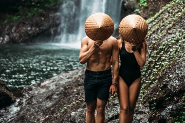 The couple travels the world. Vacation in Asia. A couple in love on a waterfall. Man and woman in conical hats at a waterfall. Beautiful couple traveling in Bali. Travelers at the waterfall.