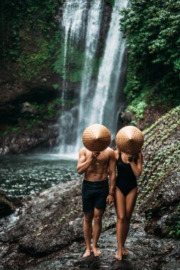 A man and a woman in conical hats at a waterfall. The couple travels the world. Vacation in Asia. A couple in love on a waterfall. Beautiful couple traveling in Bali. Travelers at the waterfall.