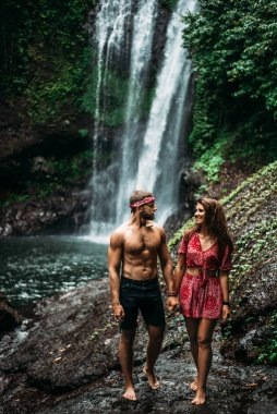 An athletic man holds the hand of a beautiful woman at a waterfall. A couple in love on a waterfall. Honeymoon trip. Happy couple in Bali. Beautiful couple travels the world. Lonely couple in love