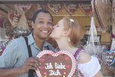 Junger Mann bekommt einen Kuss, weil er seinem Date ein traditionelles Oktoberfest-Lebkuchenherz schenkt