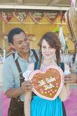 Ehepaar mit traditionellem Oktoberfest-Lebkuchenherz