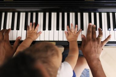 Toddler learning to play piano with father