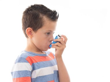young boy using an inhalator while having an asthma attack to improve his breathing