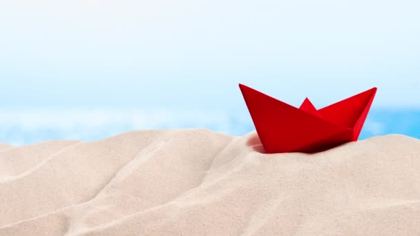 On the Beach - red paper boat on a sand dune in front of beautiful azure sea on a sunny day  - seamless loop