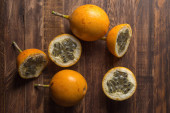 Sweet granadilla or grenadia passion fruit. Whole and cut in half exotic fruits on wooden board