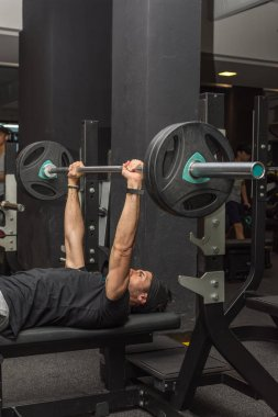 Sports young latin man lifting barbell in a gym. Gym chest exercises. Selective focus