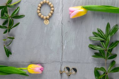 Jewelry, bracelet with keychain and gold earrings together with tulips and green laid on a concrete background. Inside the composition, free space.