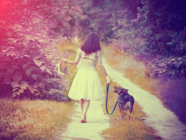 Young bride walking barefoot with dog on rural road