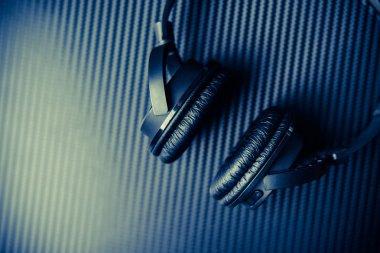 Wireless headphones on carbon background.