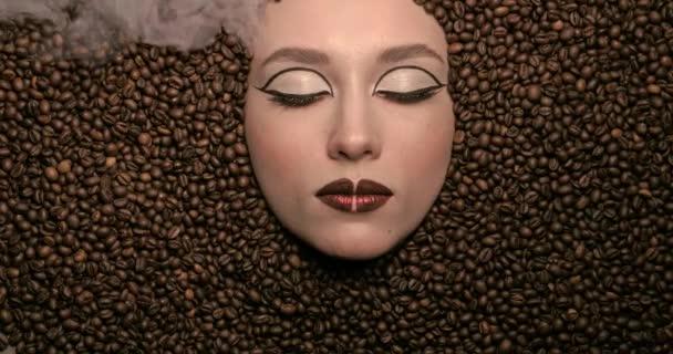 Detail portrét krásné mladé dívky s kávovými zrny kolem její lehké páry. Vysoce módní modelka krásná hnědá make-up. dívám se do kamery. Kafe životní styl. Vysoce kvalitní video 4k