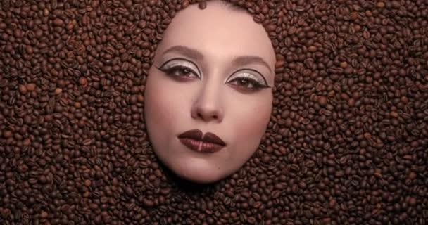 zblízka portrét krásy mladá žena tvář topí v kávových zrn s krásným hnědým make-up. Vysoce kvalitní video 4k
