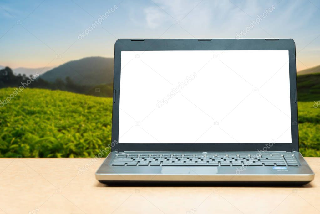 Laptop with blank screen on table with blur green nature