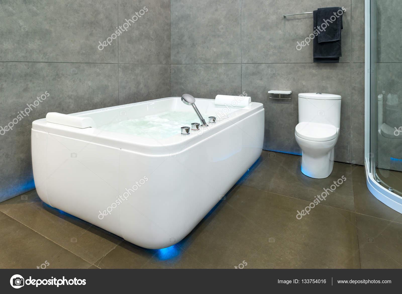 Blanc ronde jacuzzi avec une eau tourbillonnante dans salle de bains ...