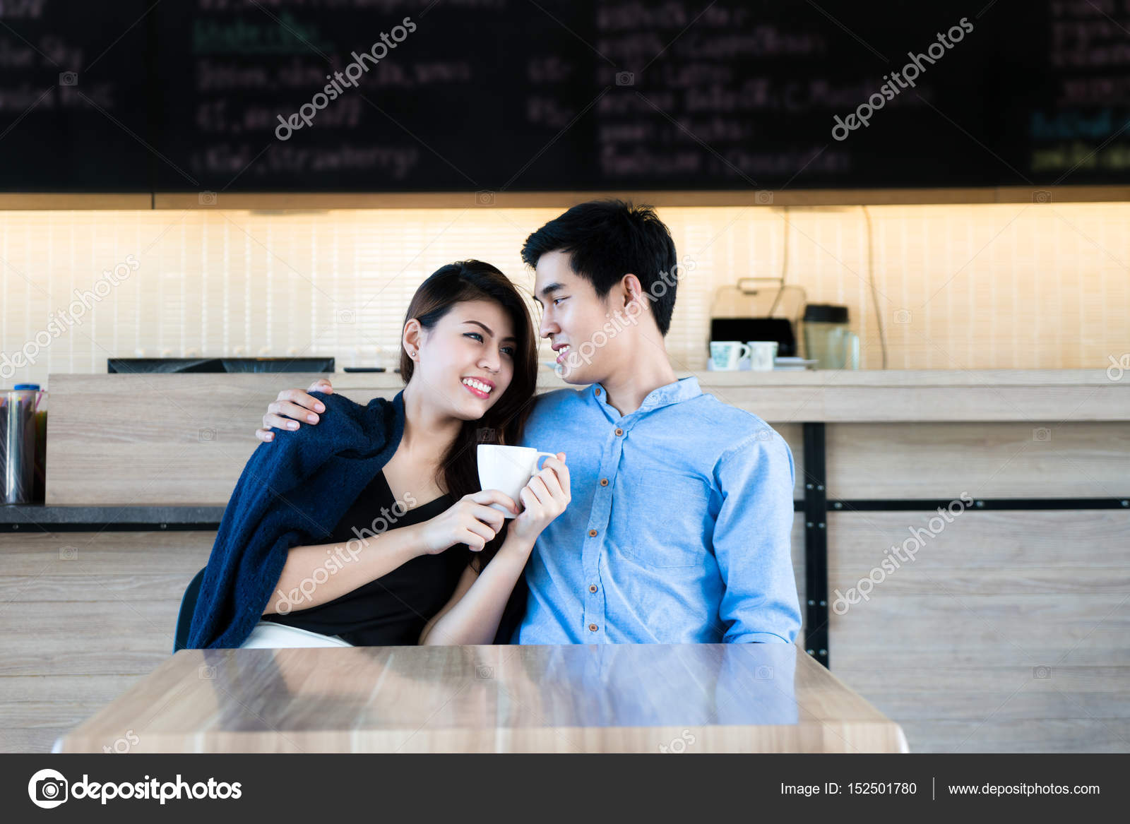 Asian beautiful young couple sitting in a cafe, drinking coffee and enjoying  the conversation. Romantic couple dating in the cafe.