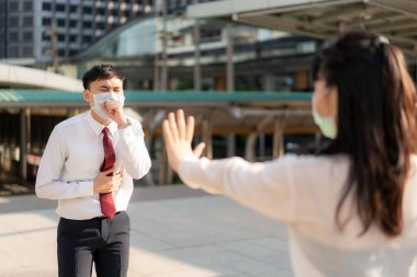 Asian ill businessman cough with mask and businesswoman stop sign hand him to keep distance protect from COVID-19 viruses and people social distancing for infection risk and disease prevention measures