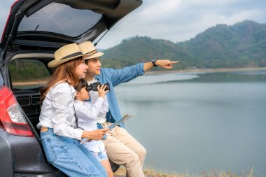 Portrait of Asian family sitting in car with father pointing to view and mother holding maps with daughter looking beautiful landscape through binoculars while vacation together in holiday. Happy family time.