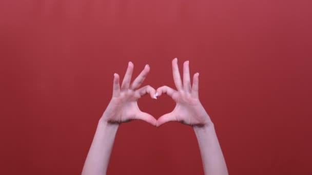 Frau macht Zeichen Herzform von Hand posiert auf rotem Studiohintergrund