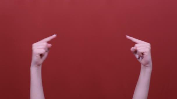 Frauenhände zeigen auf Kopierraum isoliert über pastellrotem Hintergrund