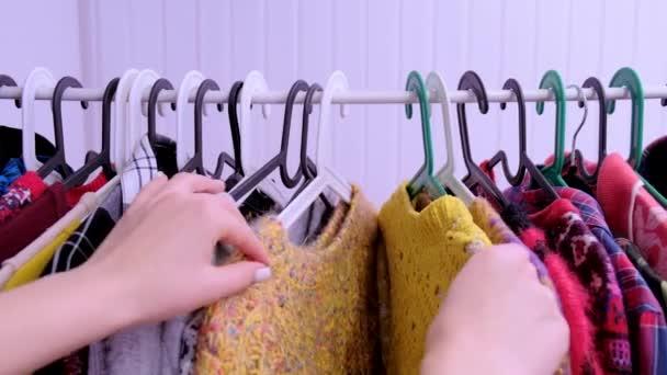 Pov. Detailní záběr ženských rukou utrhl ramínko s oblečením.