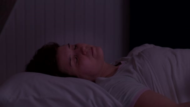 woman cant sleep from noise and covers her head with a pillow at night