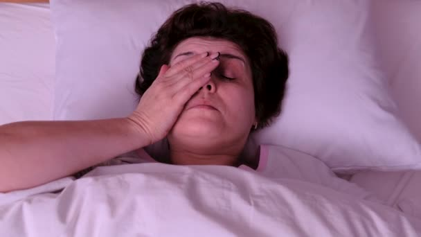 Horní pohled. Dospělá žena spí na bílém polštáři. On se probouzí..