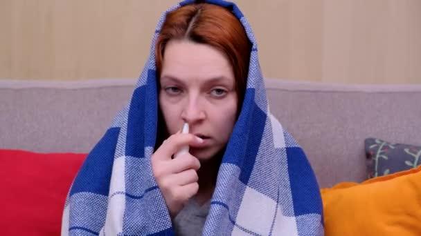 Eine Frau sitzt auf dem Sofa und sprüht sich Medikamente in die Nase. Frau krank
