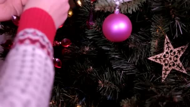 Frau händigt Christbaumschmuck mit Weihnachtsbeleuchtung aus. Konzept der Feiertage und des neuen Jahres.