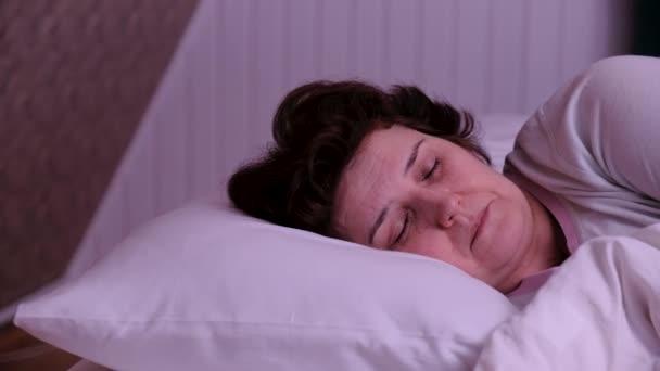 Felnőtt nő alszik egy fehér párnán.
