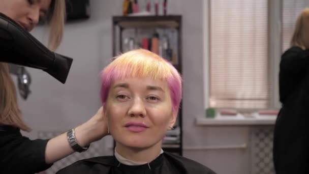 A pretty girl with short pink / multi-colored hair is blow-dried in a hair salon