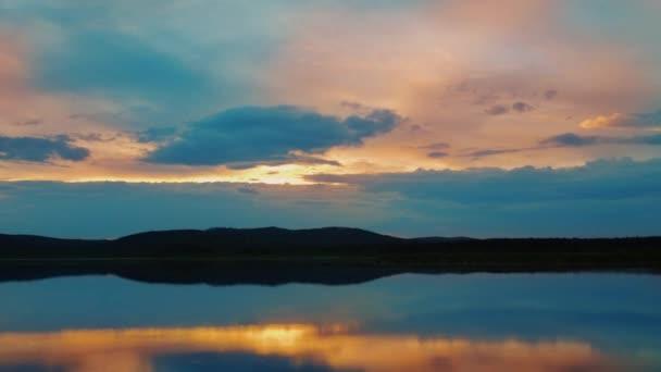 Dramatický barevný čas západu slunce. Ohnivá zatažená obloha se pohybuje nad jezerem.