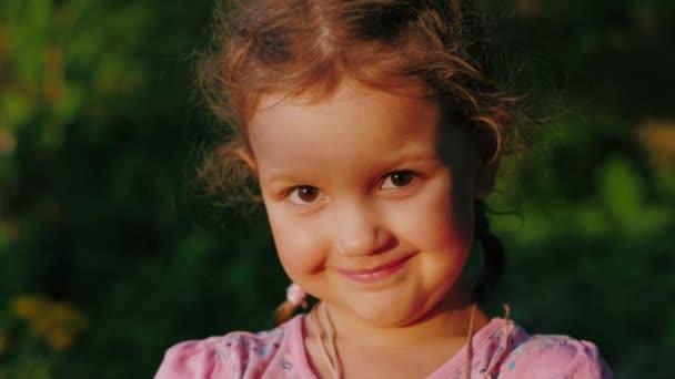 Šťastná roztomilá holčička evropského vzhledu, dívá se na kameru a usmívá se