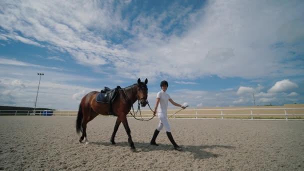 Junge Reiterin geht mit braunem Pferd an der Leine auf sandigem Reitplatz