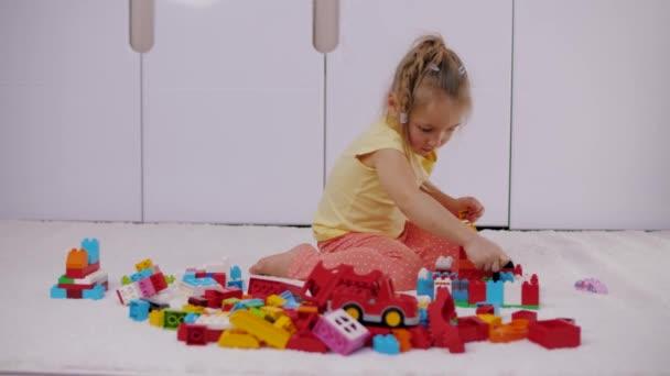 Malá holka sedí na koberci a hraje si s barevnými lego stavební bloky