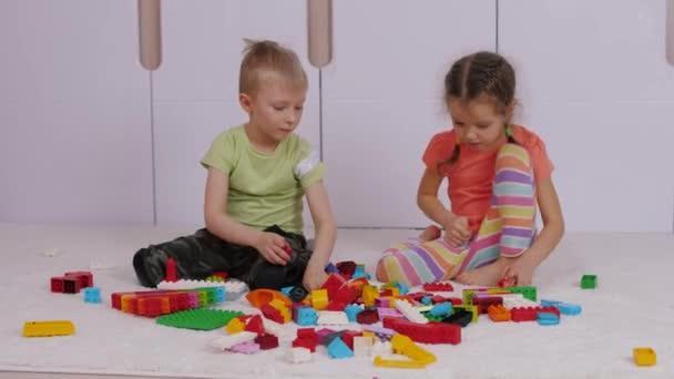 Děti sedí na koberci a hrají si s barevnými lego stavebními kameny