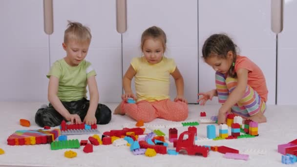 Children sitting on carpet in playroom and playing with constructor lego bricks