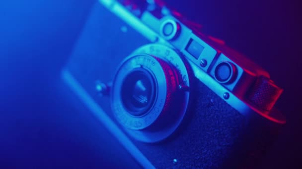 Vintage photo camera in neon blue light, smooth cinematic motion, filmic haze