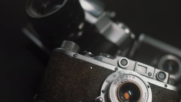 Vintage film photo camera lies in background of other old analog cameras