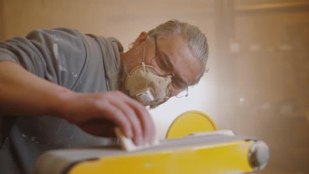 Tesař používá elektrickou brusku k leštění dřevěné části nábytku