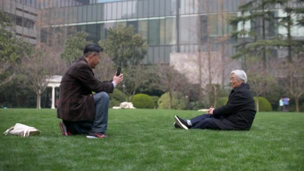 Chinese Man Takes a Photo of his Mother with a Phone on the Lawn