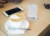 šálek kávy na dřevěný stůl na hnědé pozadí