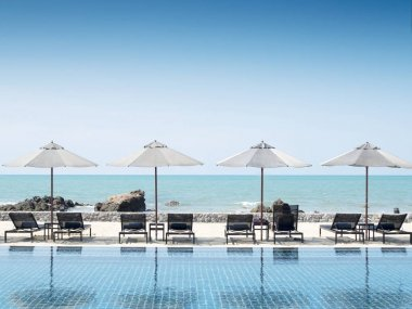Umbrella and swimming pool in hotel resort with sea beach backgr
