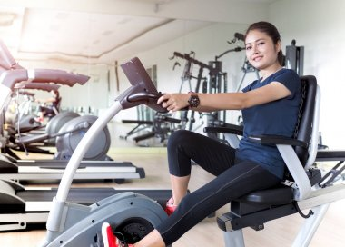Asian woman riding stationary bike in gym.