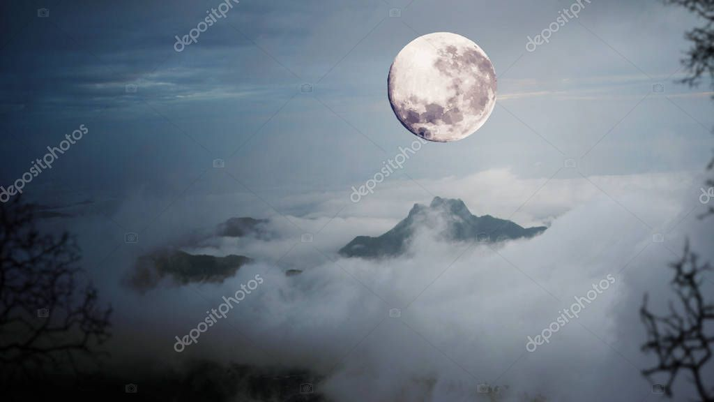 Dramatic sky with tree, full moon, fog and clouds over mountain