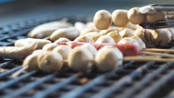 Pouliční stánky s jídlem, vaření porkballs drží na grilu