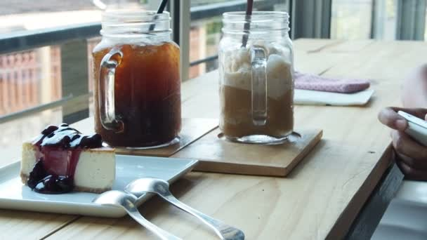 Asijské žena s smartphone, ledová káva, čaj, vodní sklo a dort v baru