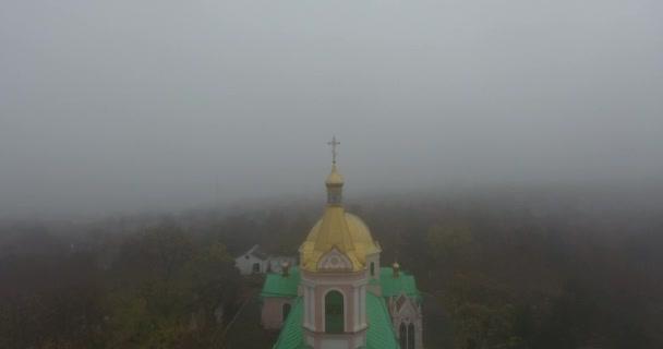 Letecký pohled na Mikulášově kostel všech svatých, město v husté mlze, Ukrajina