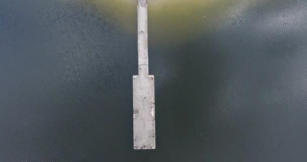 Pohled shora na betonové molo pro lodě na pláži písečné řeky. Večerní bouře