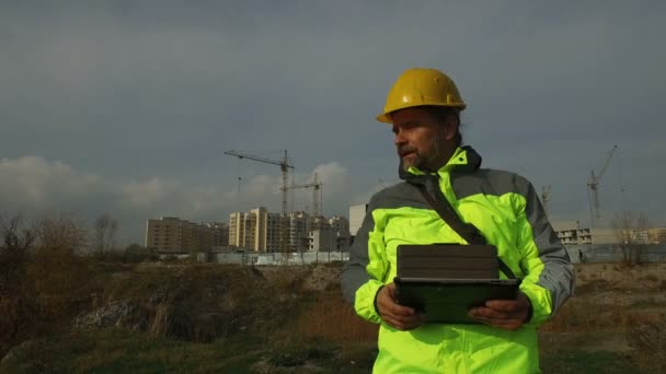 mature male worker foreman in helmet with a tablet on background of construction