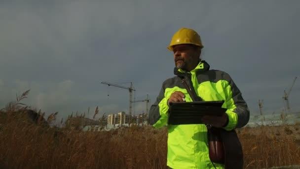 zralý muž pracovník předák v přilbě s tabletem na pozadí výstavby