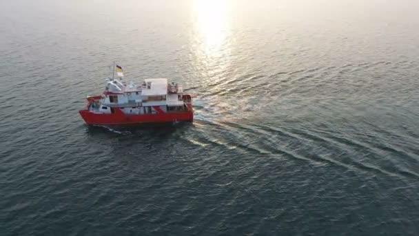 Aerial View a drónról. A vörös katamarán, a legénységgel rendelkező oceanográfiai felderítő hajó teljes lendülettel halad a nyílt tenger / óceán között